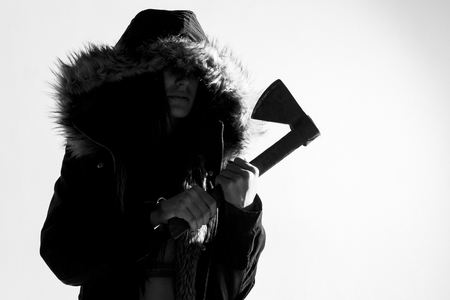 Spooky woman in a coat with fur hood, standing holding an axe. Over a white wall. Converted to black and white, grain added. Banque d'images