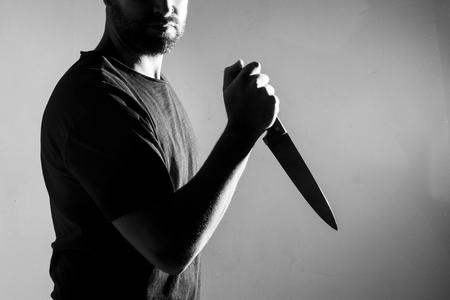 Man in zwart t-shirt, permanent met een mes. Binnenshuis. Omgezet naar zwart en wit, graan toegevoegd.