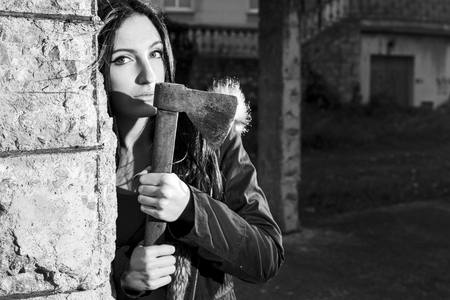 Woman escaping from someone, defending herself with an axe, outdoors, in a old construction site. Converted to black and white, grain added. Focus on the axe.