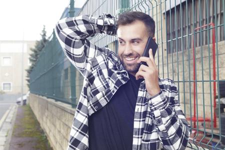 Jeune bel homme parlant au téléphone à l'extérieur, reposant sur une clôture en métal vert. Banque d'images
