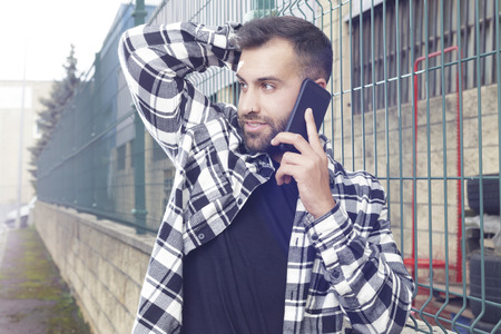 Young handsome man talking on the phone outdoors, resting on a green metal fence.