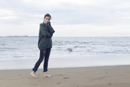 Young pretty woman standing alone on the beach near the sea, waiting for somebody in the ocean.