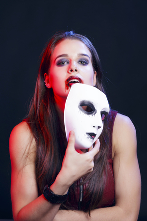 Brunette woman hiding behind a white venetian mask. She has lips in blood. Over a black background.