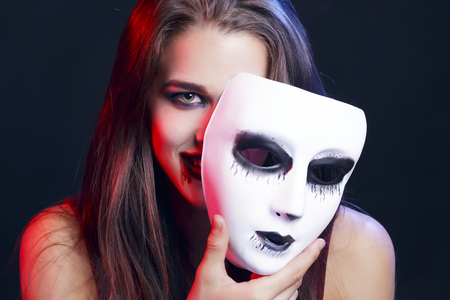 Femme brune se cachant derrière un masque vénitien blanc. Elle a des lèvres dans le sang. Sur un fond noir. Banque d'images