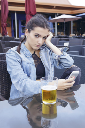 Serious girl with a beer. Sitting on a bar table outdoors, using her smart phone.