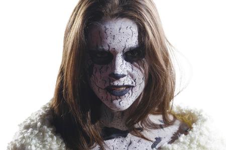 Brunette avec un visage de démon peint. Maquillage créatif dans son visage. Sur un fond blanc, isolé. Banque d'images