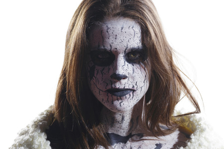 Brunette girl with a painted demon face. Creative make up in her face. Over a white background, isolated.