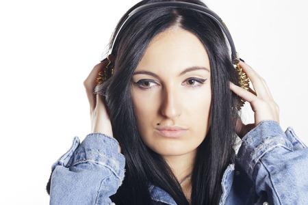 Jeune femme avec des écouteurs en épi dorés, écoute de la musique de son smartphone. À l'intérieur, sur un mur blanc.