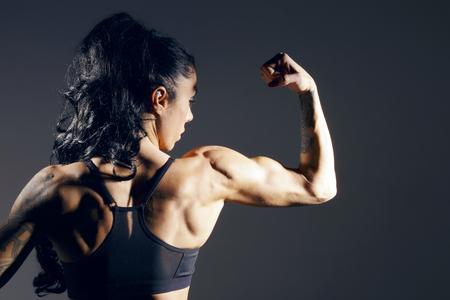 Le dos d'une femme sportive. Posant sur un mur noir.