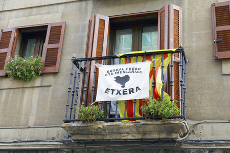 ELORRIO, SPAIN - OCTOBER 17, 2017: Balcony with a estelada, the unofficial flag flown by catalan independence supporters, and a banner asking for the approach of the basque prisoners.