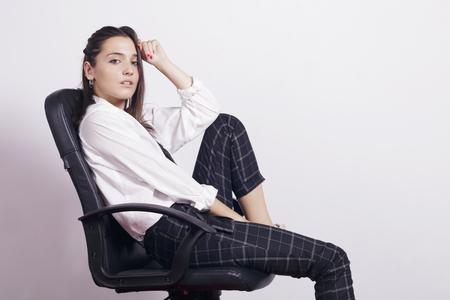 Fille portant un uniforme scolaire, assis dans une chaise de bureau. Sur un fond blanc. Banque d'images
