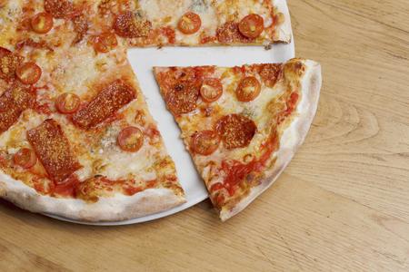 Pizza fraîche au pepperoni, tomates cerises, fromage et sauce tomate sur une table en bois rustique avec espace copie. Banque d'images