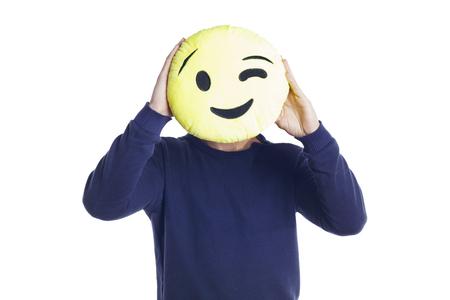 Homme debout sur un fond blanc, tenant une peluche emoji clignotante. Isolé. Banque d'images
