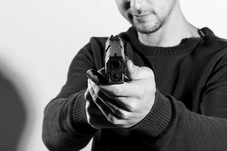 Homme tenant un pistolet, visant à la caméra. Converti en noir et blanc, grain ajouté. Banque d'images