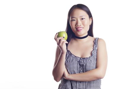 Asiat debout sur un fond blanc, tenant une pomme verte. Isolé. Banque d'images
