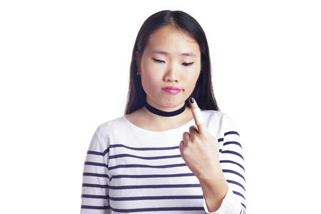 Fille asiatique inquiète sur un fond blanc, avec un pansement dans un doigt. Isolé. Banque d'images