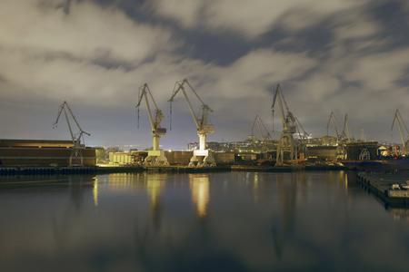 Grues monumentales au lever du soleil dans le chantier naval. Activité de nuit dans les usines navales entourant la ville de Bilbao, en Espagne.