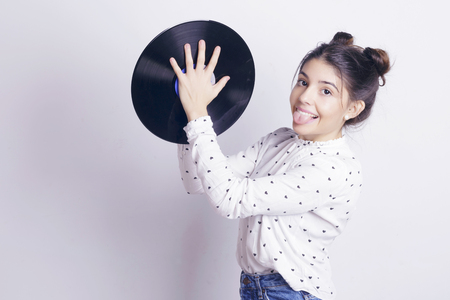 Girl holding a vinyl record, playing with it, indoors, over a white wall.