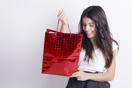 Beautiful girl holding a red shopping bag over a white wall. Banque d'images