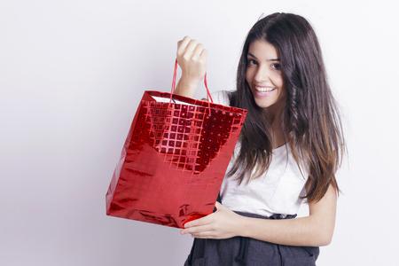 Belle fille tenant un sac shopping rouge sur un mur blanc. Banque d'images