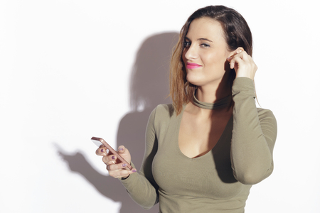 Young woman with a wireless earphone, wireless connectivity with her smartphone. Indoors, over a white background.