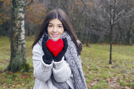 Young brunette woman holding a heart shaped cushion, outdoors, in winter mountains. Valentines day concept. Love.