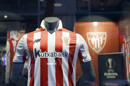 BILBAO, SPAIN - DECEMBER 23, 2017: Athletic Club soccer team shirt, taken outdoors on the storefront of the club shop.