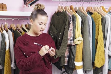 Clothing store owner labeling a sweater, putting a price tag. Banque d'images