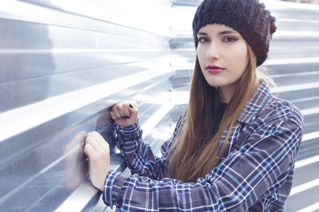 Beautiful girl with a blue checkered shirt and a beanie hat, thinking sad, leaning on a steel wall in the street.