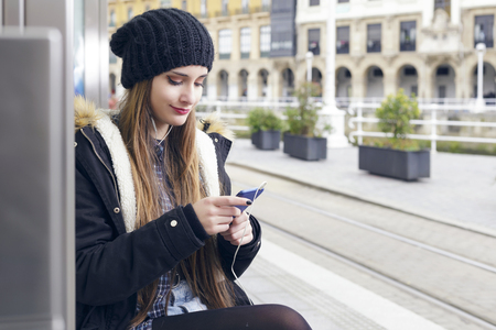 Young woman waiting on station platform, using smart phone sitting on a bench. Tourist texting message and planning route. Outdoors.