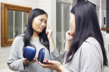 Young asian woman applies makeup in front of a bathroom mirror. Powder with brush to her skin.
