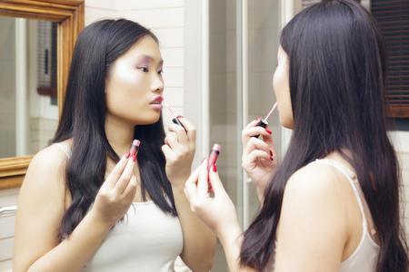 Young asian woman applies makeup in front of a bathroom mirror. Lip gloss applied to her lips