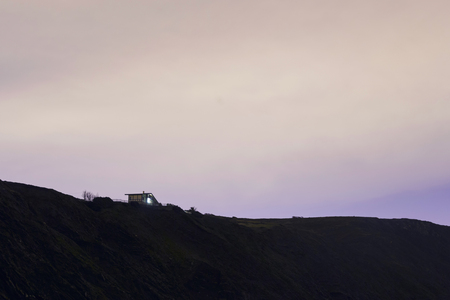 Small house near the mountains slope, at a cloudy night. Basque Country, Spain.