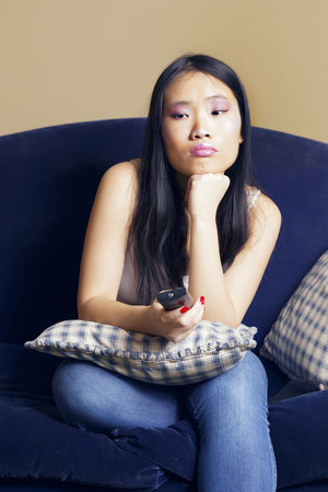 Bored asian girl sitting on a blue sofa, watching something on tv, at home, indoors.