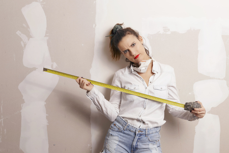 Woman with a measure tape working in a construction. Do it yourself concept.