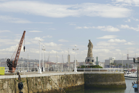 Blessed Virgin Mary statue in the fishing port of Santurtzi, Basque Country, Spain. Outdoors on a cloudy day. No people. Banque d'images