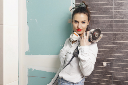 Young woman working with a angle grinder. Home improvement.