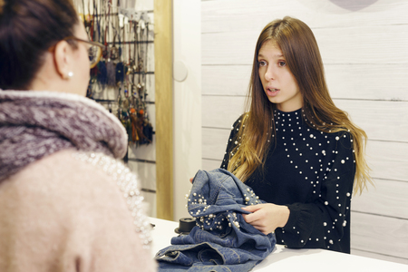 Female shop assistant talking with the customer, in the checkout of a clothing store. Something is wrong. Фото со стока