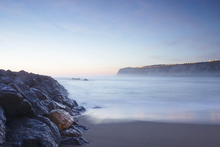 Serene seascape in Arrigunaga beach, Biscay, Basque Country, Spain. Long exposure on a misty sunset.