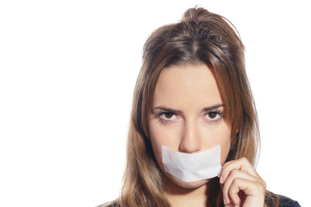 Blonde woman silenced with tape, removing it and finally free. Isolated, over a white background.