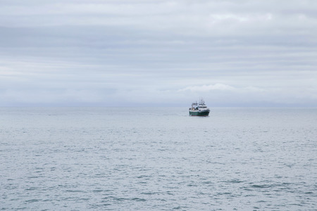 Fishing boat at sea on a cloudy morning. Alone into the big ocean.