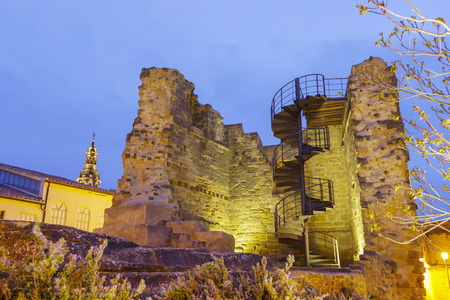 La Asuncion church in Briones, La Rioja, Spain. And the ruins of the castle of Briones. At sunset on a cloudy day.