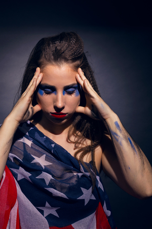 Woman covered with an american flag, worried about the future. Studio shot, in a black background.