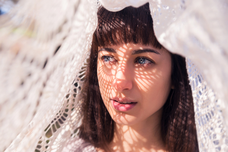 Beautiful brunette girl with a light pattern on her face in the form of a grid. Outdoors, on a sunny day.
