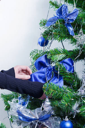 Decorated Christmas tree close up and its ornaments. Indoors, adding a blue ribbon.