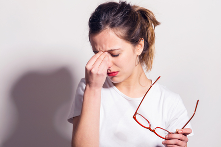 Tired young woman taking off her glasses and rubbing eyes, on a white wall background.