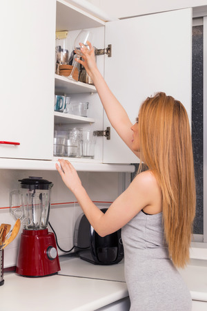 Blonde woman looking for something in her kitchen, in a closet.