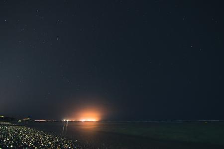 Flash in dark night sky over sea and yellow coast Stock Photo