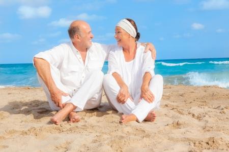 古いカップルはビーチに旅行