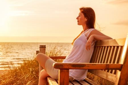 mujer meditando: relajante mujer en la puesta del sol costa